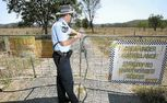 Officer-in-charge of Gracemere Police Station Sergeant Ben Holdcroft at the locked gates of the abandoned St Joseph's Orphanage at Neerkol.