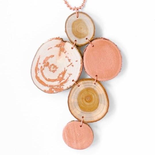 Trähalsband med kopparinslag. Halsbandet består av två kopparmålade träbrickor, två guldregn och en bit av hassel.