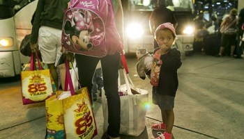 A mother and her three-year-old daughter wait for a bus in McAllen, Texas, after leaving Honduras, which has been battered by violence.