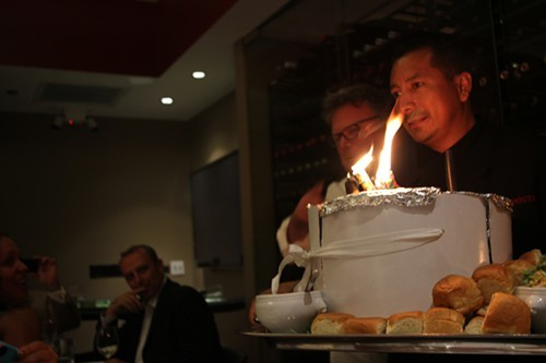 David Burke watches as the birthday cake is rolled in.