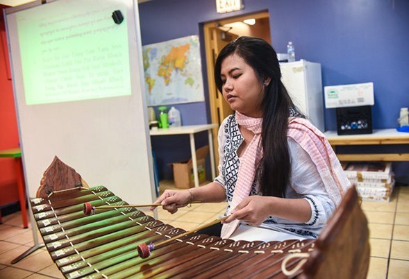 Punisa Pov leads a class at CAI while playing the roneat ek, a xylophone used in Khmer classical music.