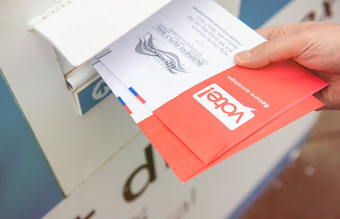 Mail-in ballot being slid into a designated drop box