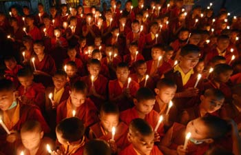 Monks hold candle light vigil to mourn the death of the 23-year-old gangrape victim