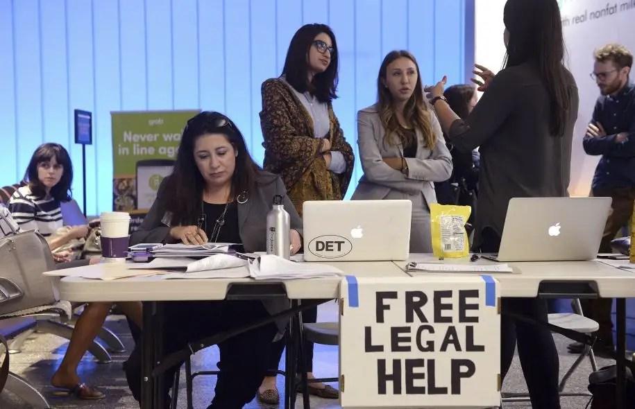 Une avocate de l'Association des avocats immigrants américains, Maggie Castillo, à gauche, offrait vendredi ses services juridiques à un kiosque improvisé à l'aéroport international de Los Angeles.