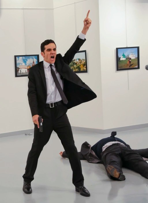 Image: An unnamed gunman gestures after shooting the Russian Ambassador to Turkey