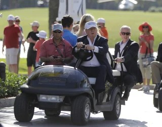 Image: Then-Republican presidential candidate Donald Trump drives himself around the golf course