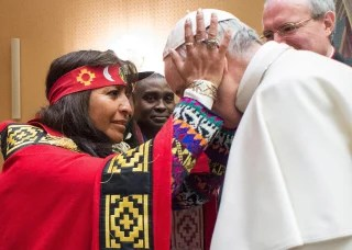 Image: A woman holds Pope Francis' head on the occasion of his meeting with representatives of indigenous peoples attending a UN agricultural meeting in Rome, at the Vatican, Feb. 15, 2017.