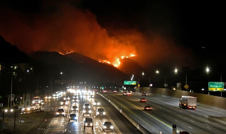 Image: The Getty Fire burns next to the 405 freeway in the hills of West Los Angeles, California