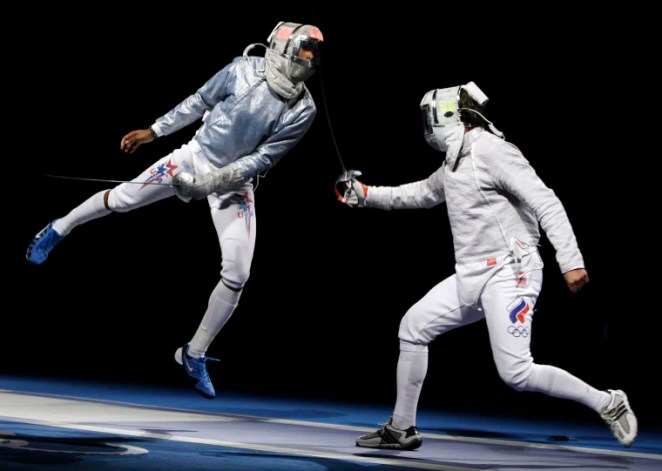 Image: Keeth Smart, left, competes against Stanislav Pozdnyakov of Russia in the semifinals of the men's team saber in fencing