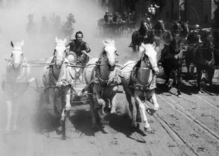 1959:  American actor Charlton Heston competes in a chariot race in a still from the film, 'Ben Hur,' directed by William Wyler.  (Photo by MGM Studio...