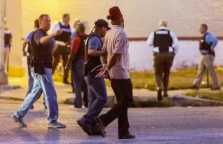Image: Police arrest a man as protesters gathered after a shooting incident in St. Louis