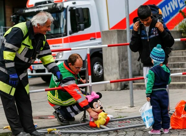 Image: Firefighters chat with migrants who arrived by train to the main railway station in Munich