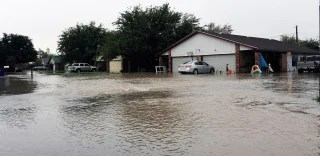 Image: Water flows into a neighborhood in Midland County