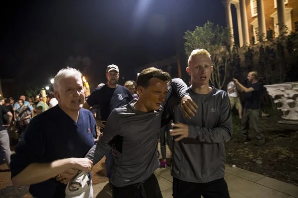 Image: A man is helped after being hit in the face with pepper spray during a clash between counter protesters and Neo Nazis, Alt-Right, and White Supremacist groups after marching through the University of Virginia Campus with torches in Charlottesville.