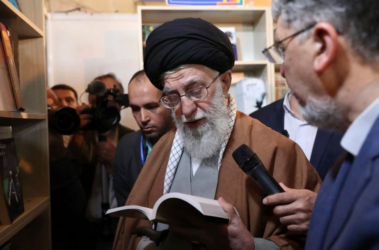 Image: Supreme Leader Ayatollah Ali Khamenei reads part of a book while visiting Tehran's book fair in Tehran, Iran