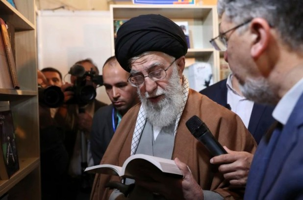 Image: Supreme Leader Ayatollah Ali Khamenei reads part of a book while visiting Tehran's book fair in Tehran, Iran