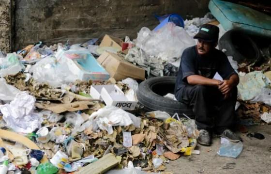 Carlos, 30, se sienta en una pila de basura donde busca comida en Caracas