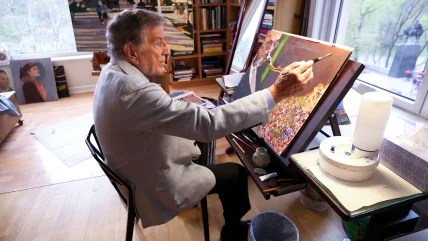 Image: In his New York art studio, Tony Bennett finishes a painting while sitting among several of his completed works.