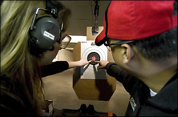 James Madison University senior Leah Sargent, 20, and instructor Carlos Santillan, 45, examine her target at the Top Gun Shooting Range in Harrisonburg, Va. The shooting session was part of a gun rights week at JMU, aimed at showing how guns could protect students when attacked, as during the Virginia Tech massacre.