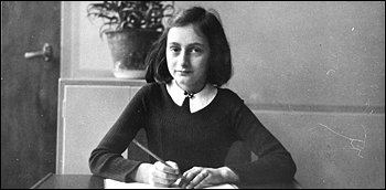 Anne Frank at age 12, sitting at her school desk in Amsterdam.