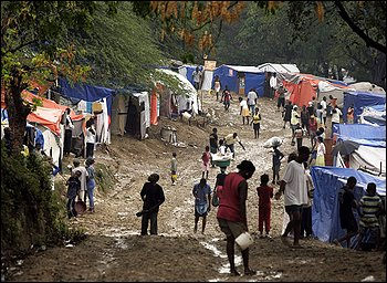 Earthquake survivors walk through the mud after heavy rains hit the makeshift tent city at the Petionville Golf Club in Port-au-Prince this month.