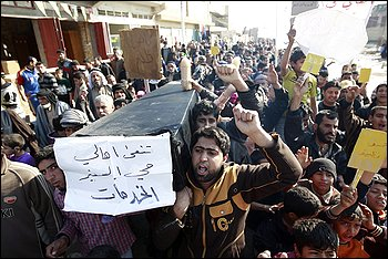 In one of many protests in Iraq's capital, Baghdad residents carry a mock coffin meant to symbolize the end of basic government services. (photo: Thaier Al-sudani)
