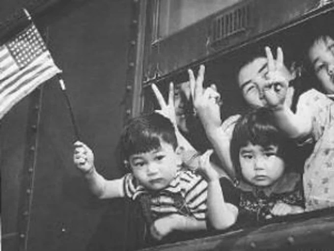 A group of Bainbridge Island Japanese residents wave from a train as they're transferred from Seattle to Owens Valley Reception Center, California, in March of 1942.