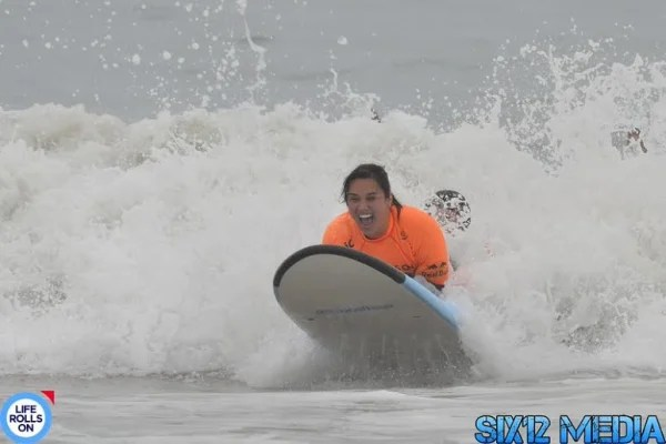 Image: Theresa de Vera surfs for the first time with Life Rolls On.