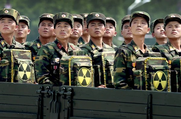 Image: North Korean soldiers turn and look towards leader Kim Jong Un as they carry packs marked with the nuclear symbol