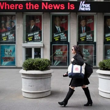 Image: A woman walks past the News Corp. headquarters