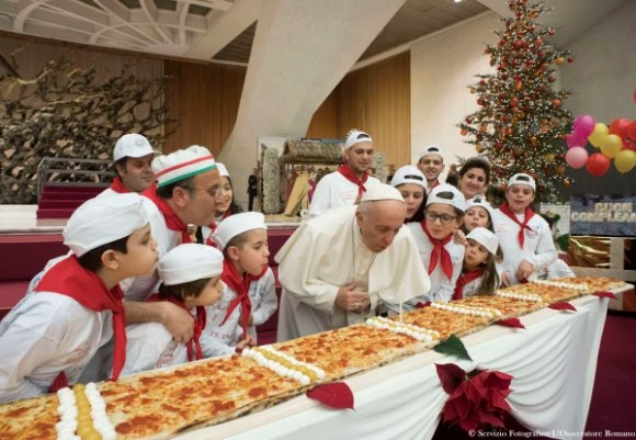 Image: Pope Francis blows out a candle on a pizza on Dec. 17, 2017 during an audience with children assisted by