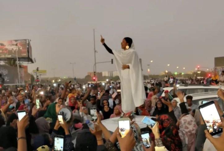 Image: A Sudanese woman gestures during a protest demanding Sudanese President Omar Al-Bashir to step down along a bridge in Khartoum