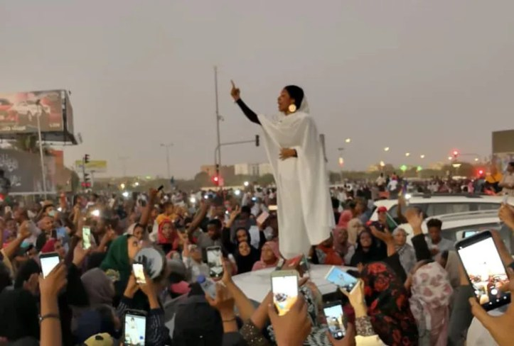 Image: A Sudanese woman gestures during a protest demanding Sudanese President Omar Al-Bashir to step down along a bridge in Khartoum