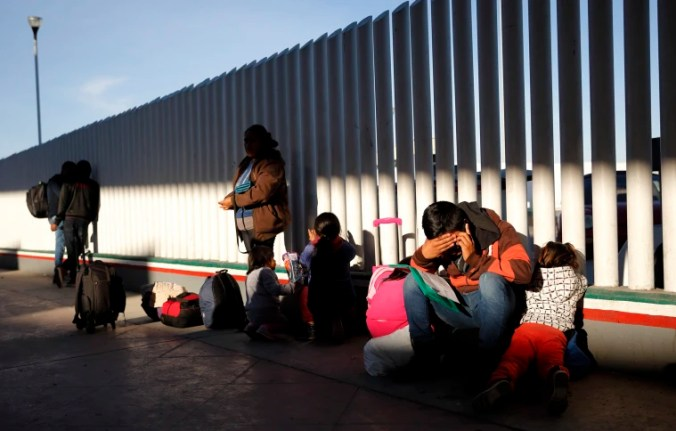 Image: A migrant sits with his children to apply for asylum to the United States at the border with Mexico in Tijuana on Jan. 25, 2019.