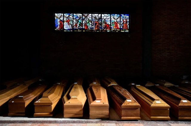 Image: Coffins of people who have died from Covid-19 are seen in the church of the Serravalle Scrivia cemetery