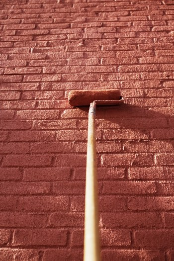 Paint roller and brick wall