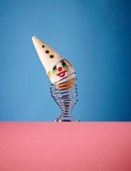 Egg painted as clown on metal egg cup --- Image by © Derek James Seaward/Corbis