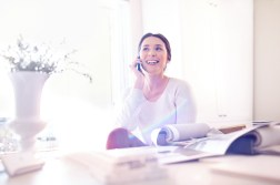 Smiling interior designer talking on cell phone in bright office