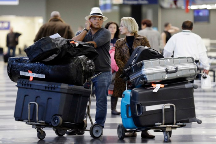 Two people at an airport with several suitcases - travel 2020