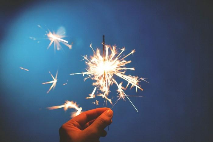 Hand holding up a sparkler firework