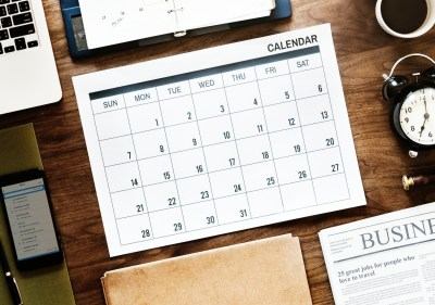 View of a calendar on top of a desk, surrounded by a laptop, clock, newspaper, and other office items