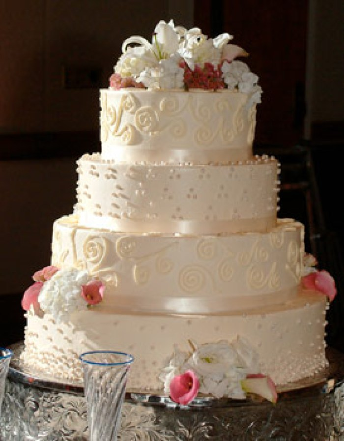 Wedding cake with flowers on top, champagne flutes in front