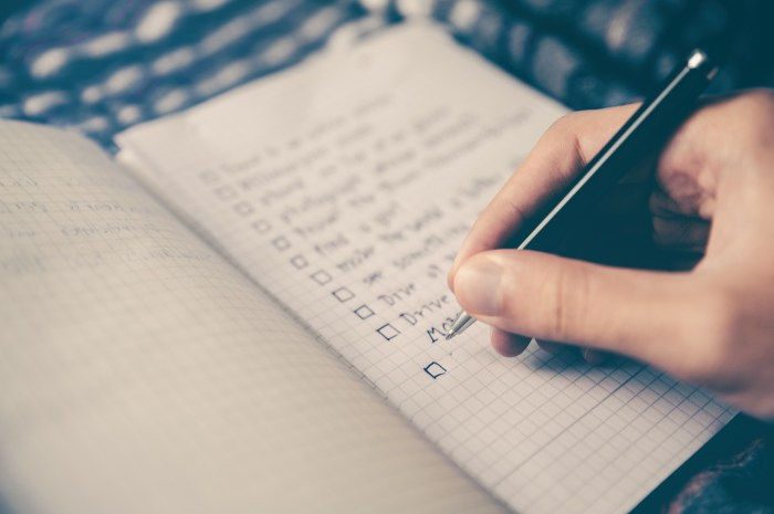 Closeup of a person writing a checklist in a notebook