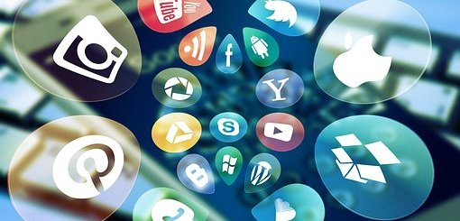 Social media icons in bubbles floating above a smartphone