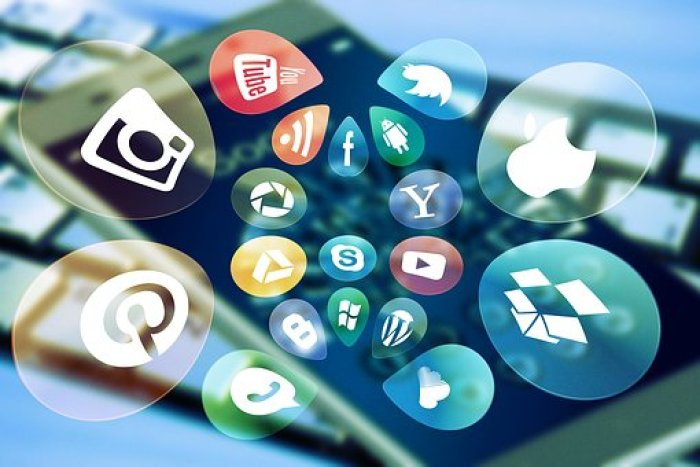 Social media icons in bubbles above a smartphone