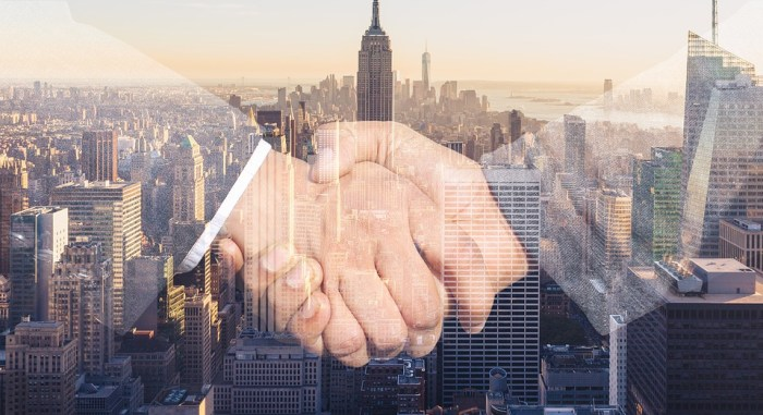 Double exposure image of a handshake over the New York City skyline