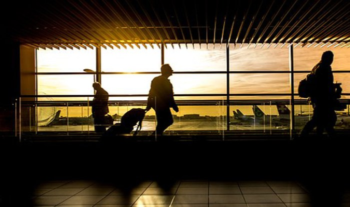 Silhouette of people walking through an airport with planes outside the window