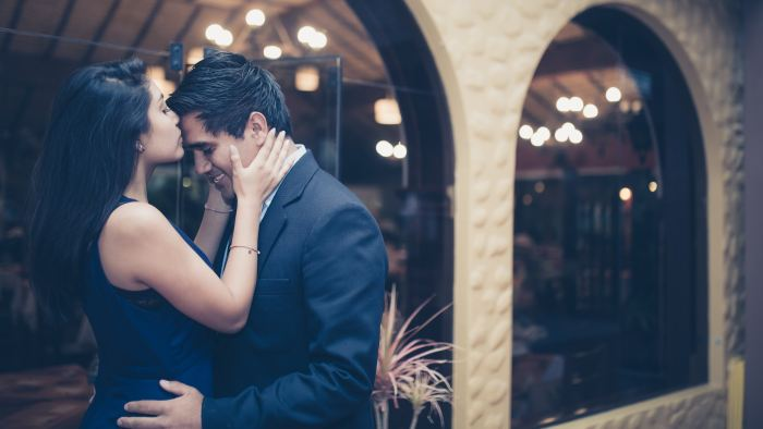 Couples Photography Tips - photo of a couple with woman kissing the man on the forehead