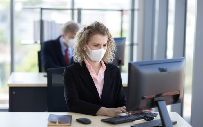 Two people wearing protective face masks in the workplace