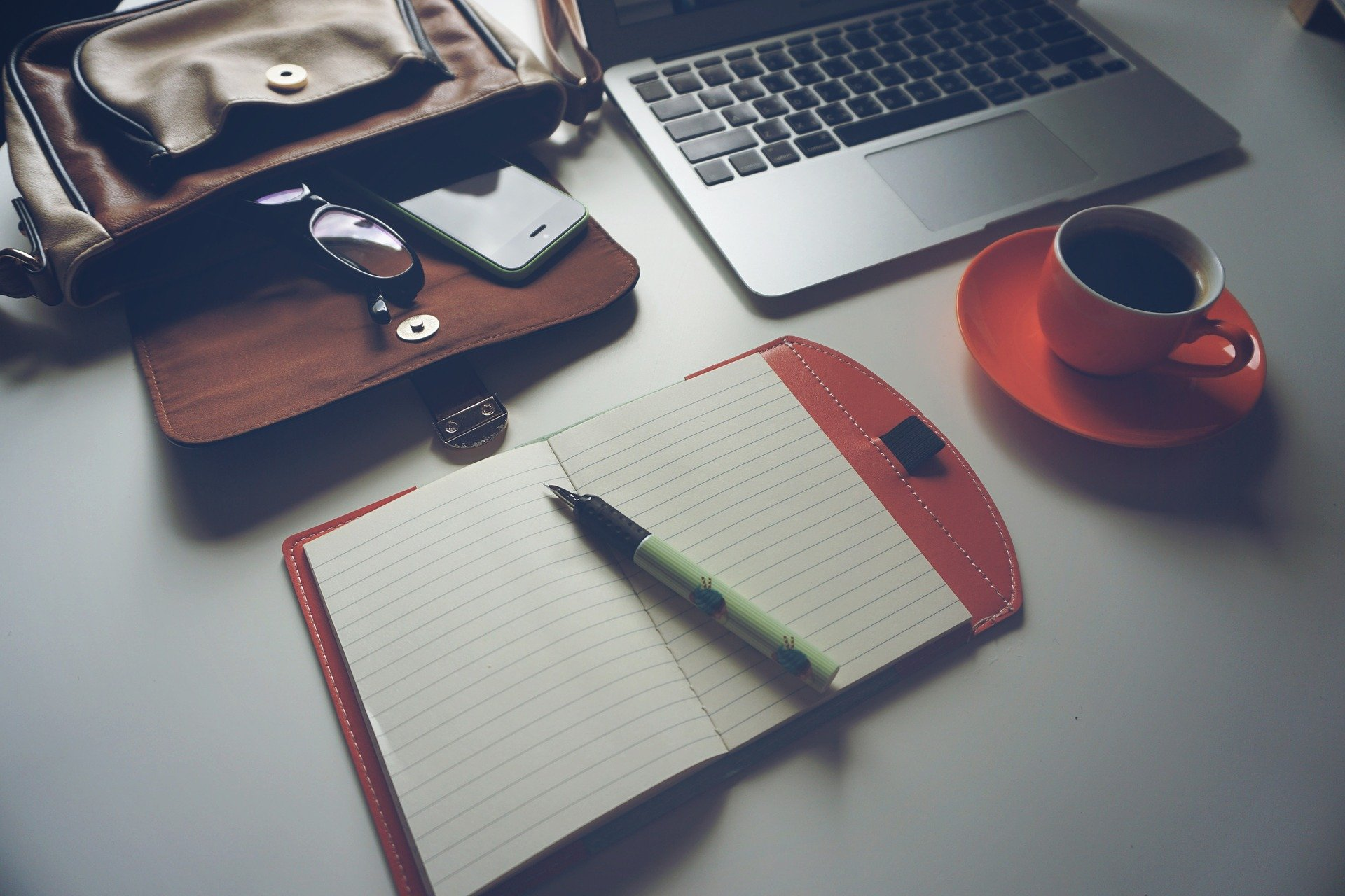 Image of a notebook, pen, laptop, coffee cup, and bag laid out on a table.